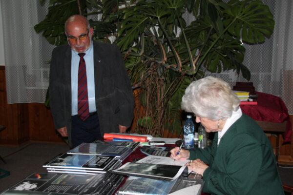 Lőwey Lilla dedikálja Mester Zoltánnak szánt ajándékkönyvet