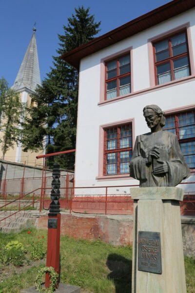 Apáczai Csere János szobra a templom és iskola előtt