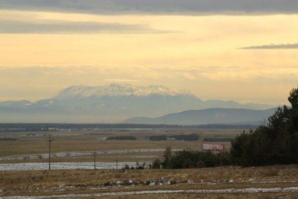 Krizba határából a Barcaságra visszatekintve látszik a hatalmas Bucsecs masszívum hófödte orma
